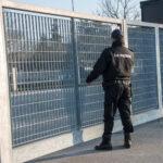 Una GPG è in piedi di fronte ad un cancello di una zona industriale voltata di schiena